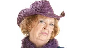 en äldre kvinna med hatt ser väldigt sur och bestämd ut medan hon tittar in i kameran.