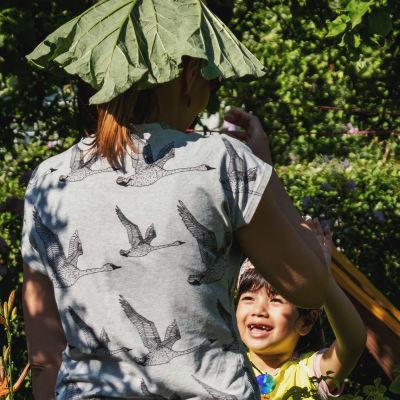 Liten flicka ler och sträcker upp armarna mot en vuxen som står med ryggen mot tittaren, och håller ett rabarberblad som hatt på huvudet.