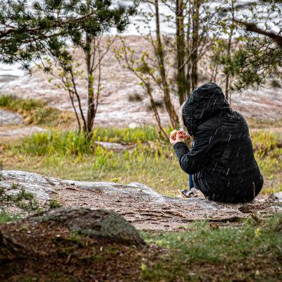 Nainen istuu räntäsateella meren rannalla ja syö munkkia.