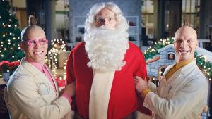 Tatu ja Patu seisovat joulupukin vieressä.