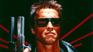 Arnold Schwarzenegger ase kädessä lähikuvassa tuhoajarobottina elokuvassa Terminator.