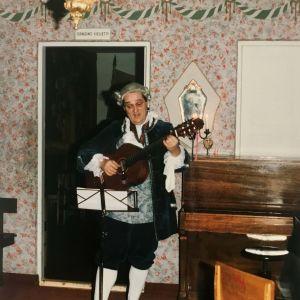 Mies soittaa kitaraa 1700-luvun juhla-asussa puuteroitu perukki päässään.