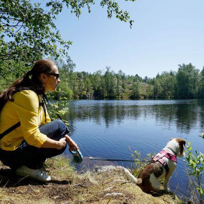 nainen ja koira järven rannalla