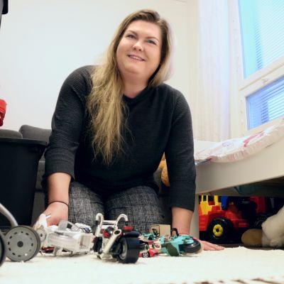 Krista Krubally istuu lasteenhuoneen lattialla ja kerää leluja.