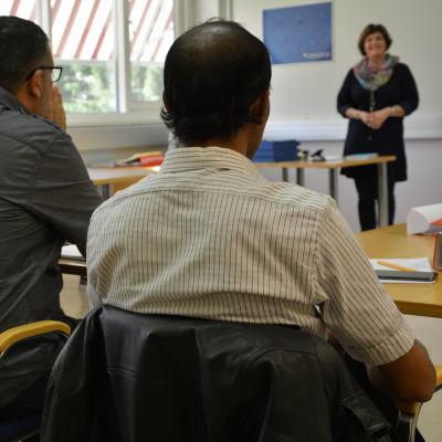 en kvinna och två män ser mot en lärare i ett klassrum