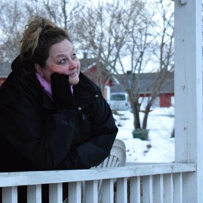 Susan Holmberg i en svart rock och lila scarf lutar mot ett vitt träräcke och tittar upp mot himlen i ett vinterlandskap.