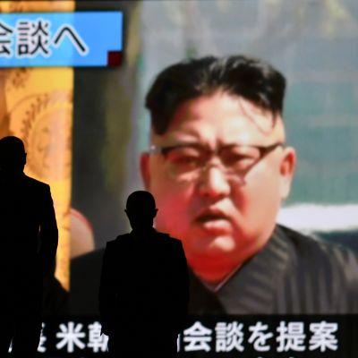 Ihmiset kävelevät suuren televisionäytön ohi. Näytöllä näkyy arkistomateriaalia Donald Trumpista ja Kim Jong-unista.