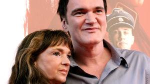 Christina Lindberg och Quentin Tarantino står bredvid varandra invid en filmplansch.