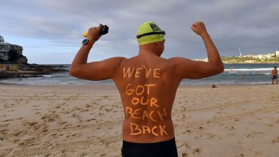 """""""Vi har fått tillbaka vår strand"""" står det på den här mannens rygg då han dyker i vid Bondi Beach i Sydney. Stranden öppnade efter att ha hållits stängd i  fem veckor."""