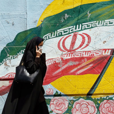 Kvinna med Irans flagga i bakgrunden.