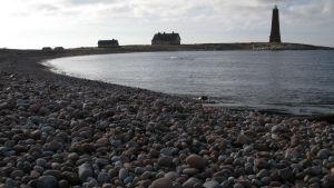 Stenig strand med en bukt. I bakgrunden en fyr och en lotsstuga.