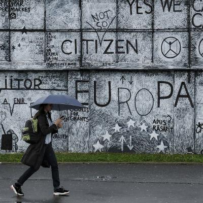 En mur med väggmålningar med EU-tema i rumänska staden Sibiu. I förgrunden en förbipasserande  invånare med ett paraply i handen.