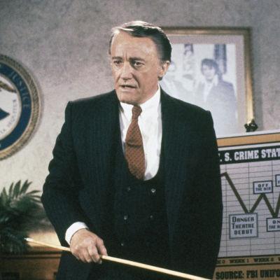 Skådespelaren Robert Vaughn står framför en graf med en pekpinne i handen.