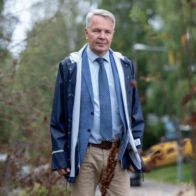Pekka Haavisto fotograferad utomhus. Han bär en regnrock ovanpå en blå kragskjorta. Han bär slips och beigea byxor.