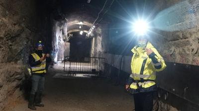 Två män med pannlampor kikar in i kameran i tunneln.