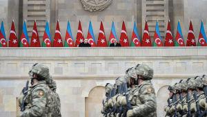 Soldater marscherar under en parad. I bakgrunden står Turkiets och Azerbajdzjans presidenter