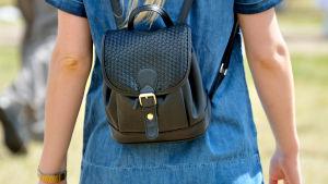 Kvinna i jeansklänning och med liten ryggsäck