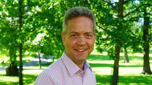 Lucas Snellman står leende i en grönskande park.