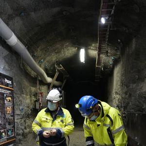 Ett hål i betonggolvet i en tunnel. Två män med stövlar och skyddsdräkter står bredvid