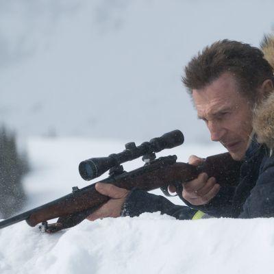 LIam Neeson ligger i snön och siktar med ett gevär.