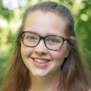 Ung kvinna med glasögon står ute i vårgrönska.