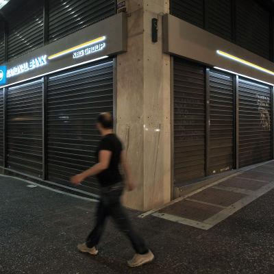 En man passerar ett stängt bankkontor i Aten den 28 juni 2015.