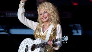 Dolly Parton med gitarr på konsertestraden.