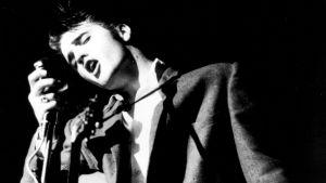 Nuori Elvis lavalla puolilähikuvassa. Kuva dokumenttielokuvasta Seitsemän kertaa Elvis.