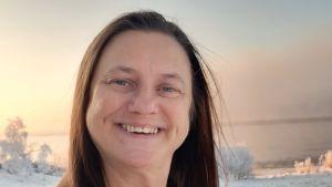 Nainen hymyilee lumisessa maisemassa