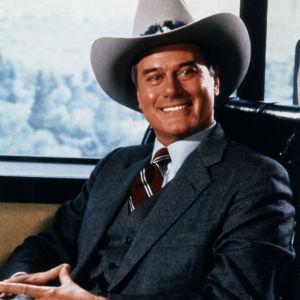 JR Ewing i stetson bakom sitt skrivbord på officen med brett dollarleende.