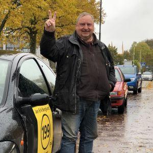 Jan-Erik Berglund gör segertecknet framför bil med kandidatreklam i regnigt Mariehamn