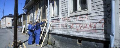 Vallattu talo Inarintiellä Helsingin Vallilassa, rakennusmiehet kiinnittävät lautoja autiotalon ikkunoihin estääkseen talon käytön (1985)
