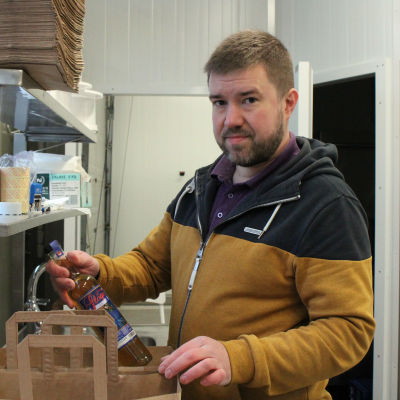 Kauppias Teemu Virrantalo pakkaa glögipullon paperikassiin.