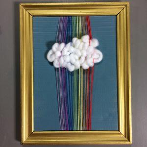 En guldram med blåmålad pappskiva och varptrådar i regnbågens färger och ett vitt fluffigt moln vävt mellan trådarna.