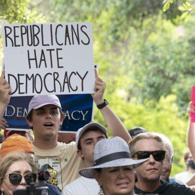 """Lippalakkiin pukeutunut valkoinen mies mielenosoittaa. Kyltissä lukee englanniksi """"republicans hate democracy""""."""