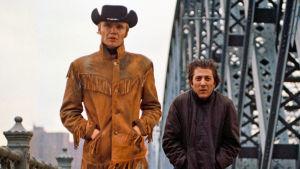 Joe Buck (Jon Voight) ja Ratso Rizzo (Dustin Hoffman) kävelevät sillalla New Yorkissa. Elokuvan Keskiyön cowboy mainoskuva.