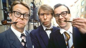 Pasi Heikura, Jyrki Liikka ja Simo Frangén. Kaikilla miehillä on piippu suussaan.