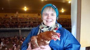 Toimittaja Reetta Arvila kana sylissään luomukanalalla.