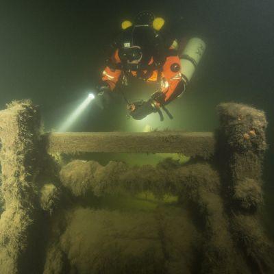 Sukeltaja tutkii Sipoon vesiltä löydetyn lähes täydellisesti säilyneen siipiratashinaajan hylyn ankkuripeliä