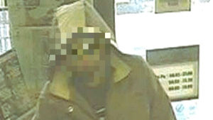 Personen med pixelerat ansikte som stiger in i en kiosk.
