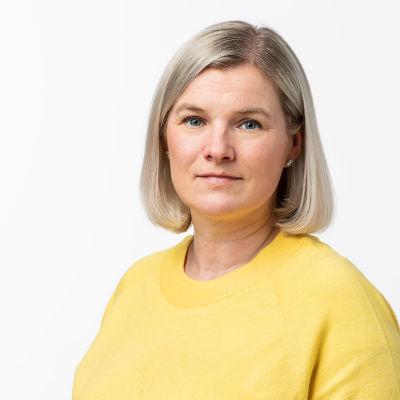 Studiofoto av producent Anki Karhu i en gul tröja.