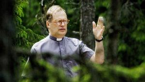 Hartaustilaisuus ulkona luonnossa, metsässä. Pappi siunaa läsnäolijoita