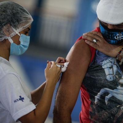 En man får en dos av Astra Zenecas coronavaccin i Brasilien