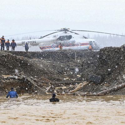 Kaksi ihmistä kahlaa syvällä vedessä. Taustalla pelastushenkilöstöä ja helikopteri.