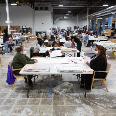 Valarbetare sitter runt bord och räknar röster.