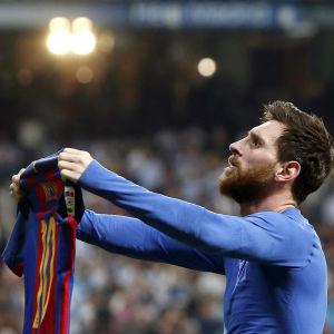 Lionel Messi håller fram sin tröja.