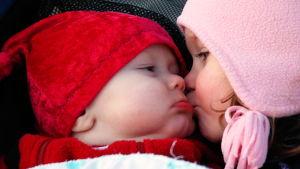 Barn som pussar en bebis.