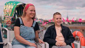 Äiti ja poika istuvat iloisina helsinkiläisessä rantamaisemassa värikäs riksa takanaan.