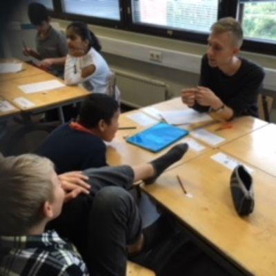 Lapsia istumassa pulpeteissa, opettaja istuu myös