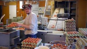 Taavi Salakka pakkaa kananmunia kennoihin.